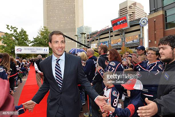 Curtis McElhinney of the Columbus Blue Jackets highfives fans as he walks into the stadium prior their home opener against the New York Rangers on...