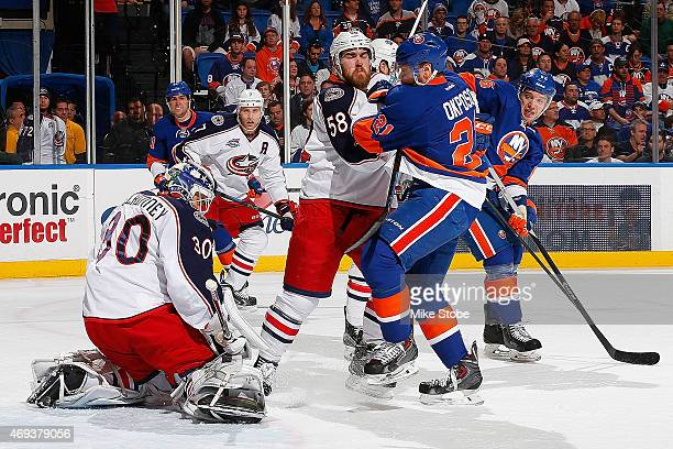 Curtis McElhinney of the Columbus Blue Jackets tends to net as David Savard of the Columbus Blue Jackets and Kyle Okposo of the New York Islanders...