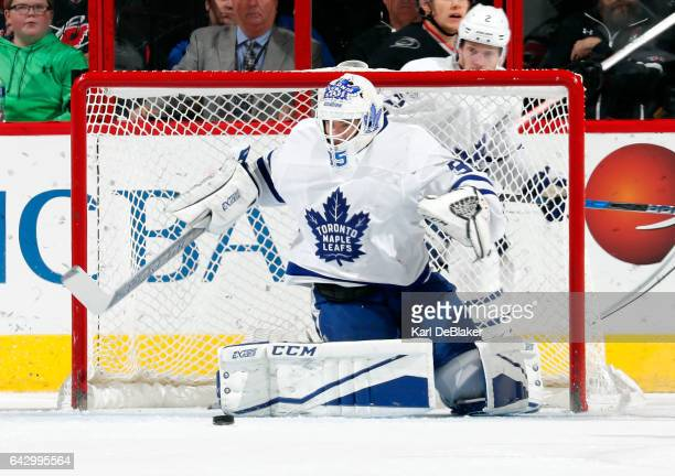 Curtis McElhinney of the Toronto Maple Leafs deflects a Carolina Hurricanes shot during an NHL game on February 19 2017 at PNC Arena in Raleigh North...