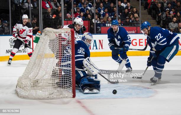 Curtis McElhinney of the Toronto Maple Leafs makes a save with teammates Nikita Zaitsev and Matt Hunwick against the New Jersey Devils during the...