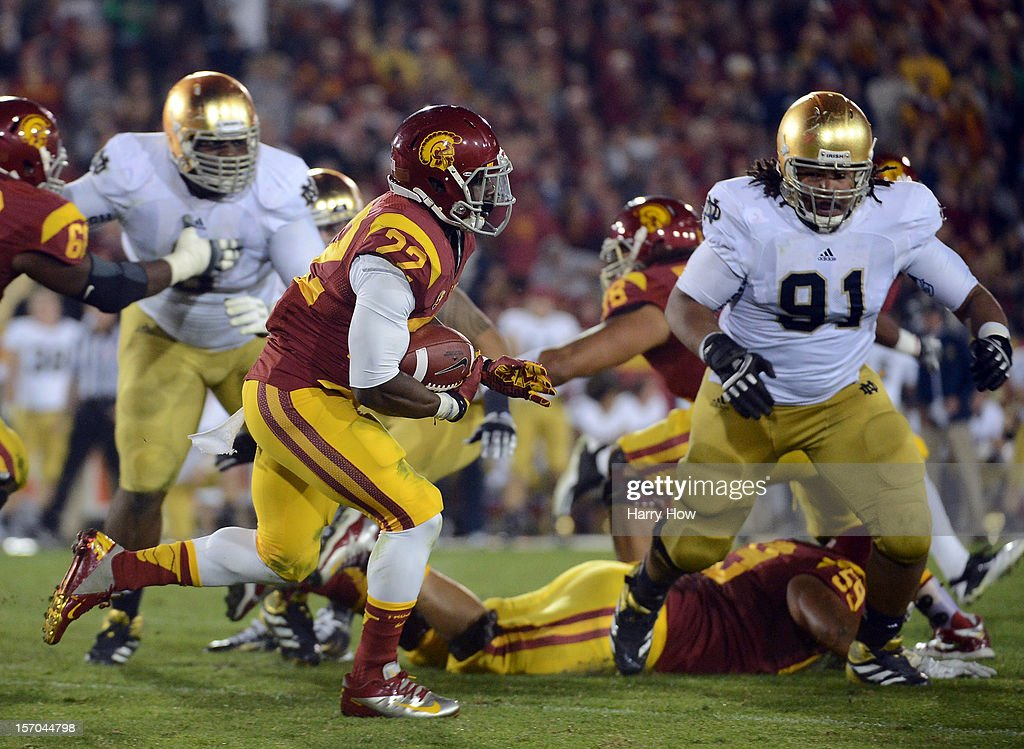 Curtis McNeal #22 of the USC Trojans rushes as he is chased by Sheldon Day #91 of the Notre Dame Fighting Irish during a 22-13 Notre Dame win at Los Angeles Memorial Coliseum on November 24, 2012 in Los Angeles, California.