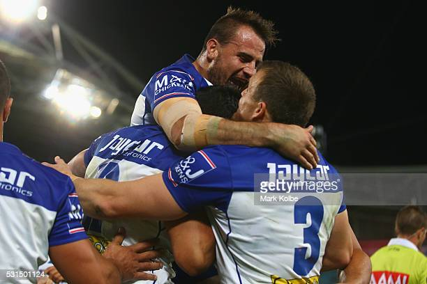 Curtis Rona of the Bulldogs celebrates with his team mates Josh Reynolds and Josh Morris of the Bulldogs after scoring a try during the round 10 NRL...