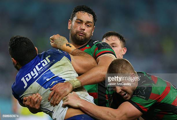 Curtis Rona of the Bulldogs is tackled by John Sutton of the Rabbitohs during the round 26 NRL match between the Canterbury Bulldogs and the South...