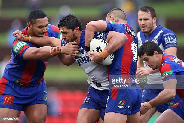 Curtis Rona of the Bulldogs is tackled by the Knights defence during the round 22 NRL match between the Newcastle Knights and the Canterbury Bulldogs...