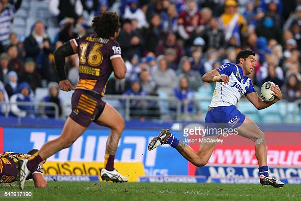 Curtis Rona of the Bulldogs makes a break during the round 16 NRL match between the Canterbury Bulldogs and Brisbane Broncos at ANZ Stadium on June...