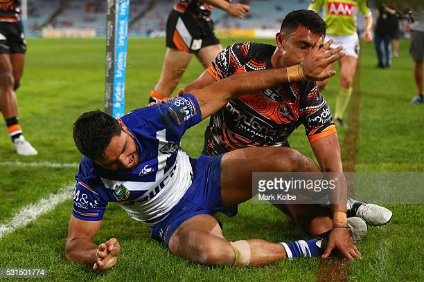 Curtis Rona of the Bulldogs pushes awayt2 of the Tigers as he clebrates scoring a try during the round 10 NRL match between the Wests Tigers and the...