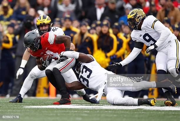 Curtis Samuel of the Ohio State Buckeyes is tackled by Taco Charlton of the Michigan Wolverines during the first quarter of their game at Ohio...