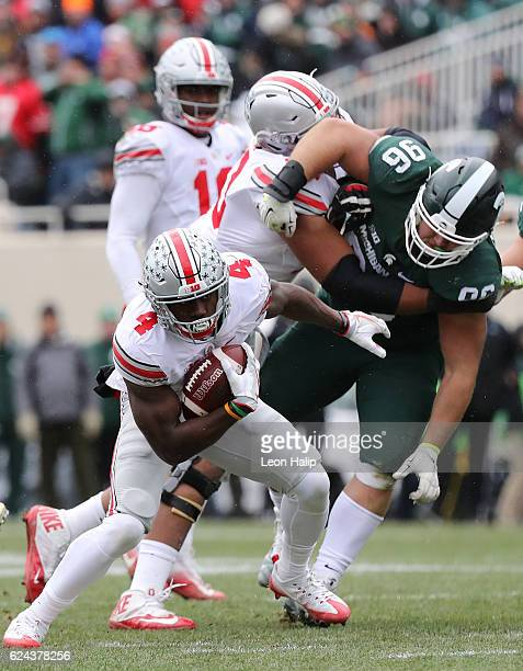 Curtis Samuel of the Ohio State Buckeyes runs for a short gain as Mike Panasiuk of the Michigan State Spartans makes the stop during the second...