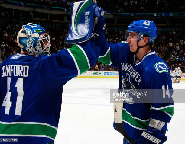 Curtis Sanford of the Vancouver Canucks is congratulated by teammate Alex Burrows during their game at General Motors Place on December 17 2008 in...