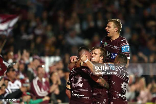 Curtis Sironen of the Sea Eagles is congratulated by Jake Trbojevic of the Sea Eagles and team mates after scoring a try during the round 26 NRL...