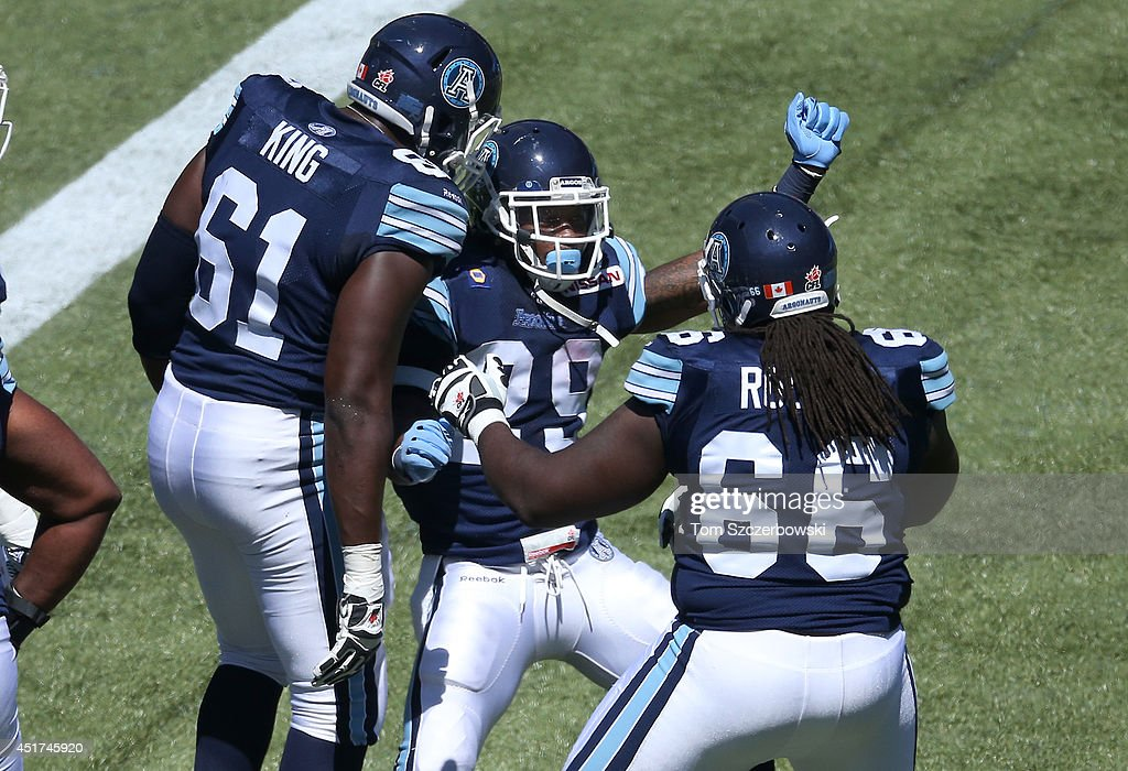 Curtis Steele #29 of the Toronto Argonauts celebrates his touchdown with SirVincent Rogers #66 and Jarriel King #61 during a CFL game against the Saskatchewan Roughriders on July 5, 2014 at Rogers Centre in Toronto, Ontario, Canada.