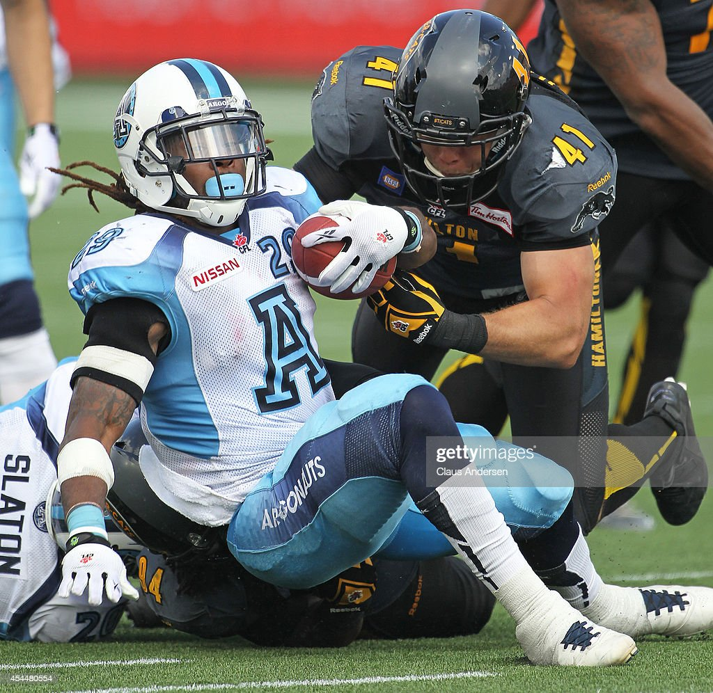 Curtis Steele of the Toronto Argonauts is tackled by Erik Harris of the Hamilton Tigercats in a CFL football game at Tim Hortons Field on September 1...