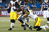 Curtis Steele of the Toronto Argonauts runs the ball as he is tackled by Erik Harris of the Hamilton TigerCats and Beau Landry of the Hamilton...