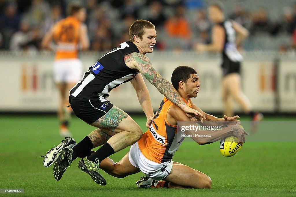 Curtly Hampton of the Giants is tackled by Dayne Beams of the Magpies during the round 18 AFL match between the Collingwood Magpies and the Greater Western Sydney Giants at Melbourne Cricket Ground on July 27, 2013 in Melbourne, Australia.