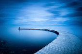 Man Standing on the Curve of the Jetty.