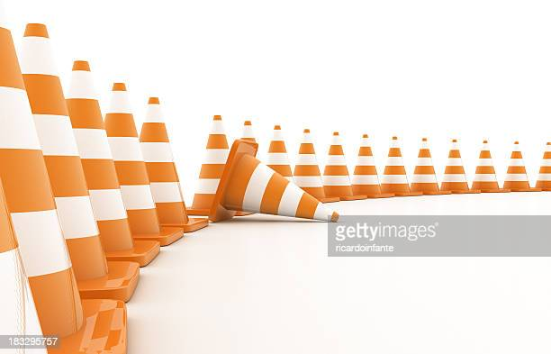 Curved line of orange traffic cones with one knocked over