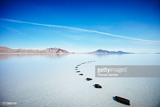Curved path of stones in calm lake