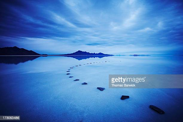 Curved stone pathway in calm lake at sunrise