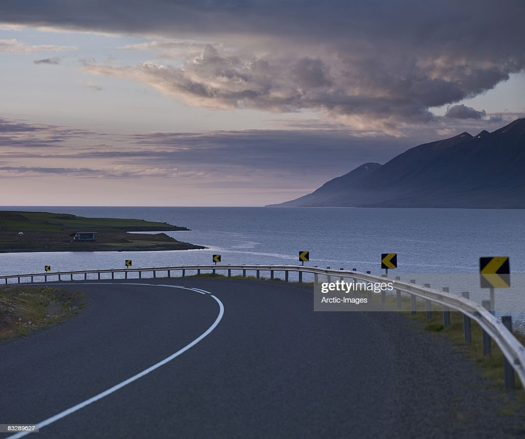 Curving road with fjord in background : Stock Photo