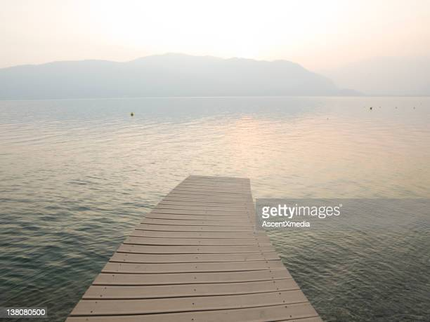 Curving wharf stretches into tranquil lake waters