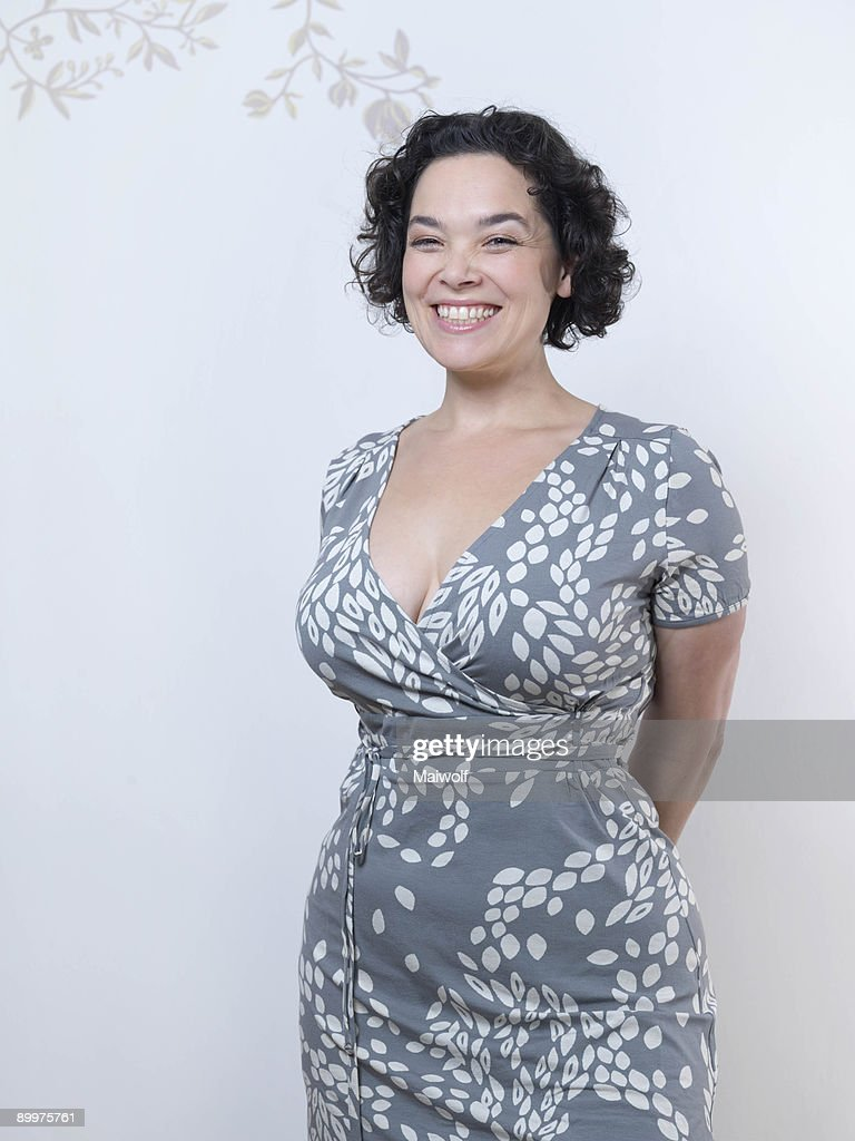 Curvy Woman standing up and smiling.