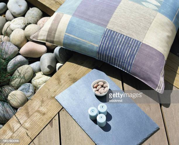 A cushion and rocks on a sunny patio