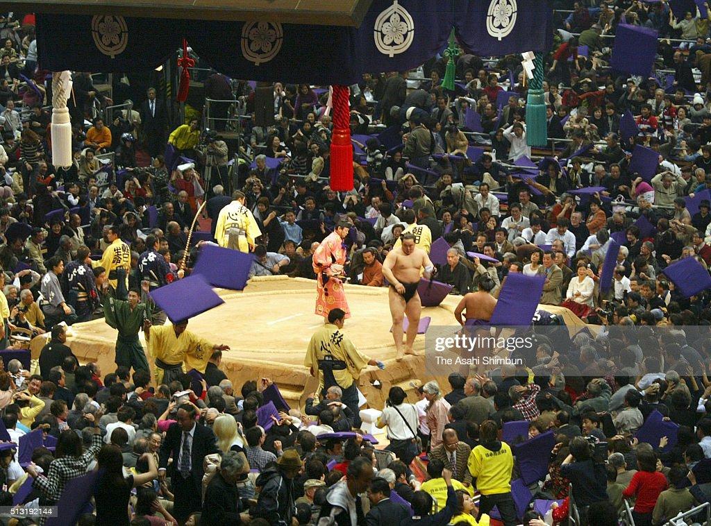 Cushions are thrown toward the ring after Mongolian yokozuna Asashoryu winning the tournament during day fourteen of the Grand Sumo Kyushu Tournament...