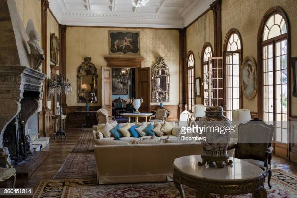 Cushions rest on sofas as 19th century portraits in ornate frames adorn the walls of a sitting room inside the Villa Les Cedres a...
