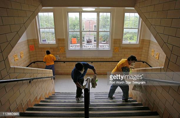 Custodians Necie Homer from left Eliseo Orozco and Modie Jarvis sanitize a stairway at Arlington Heights High School in Fort Worth Texas in an effort...