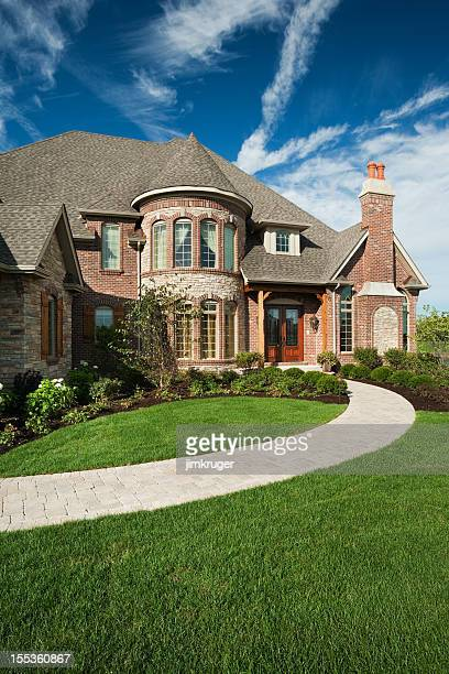 Custom built brick home on summer day.