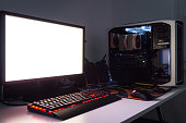 Custom built gaming computer with white screen, keyboard, mouse, joypad, gaming chair under low light. Selective focus.