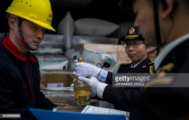 Custom officers check a bottle of Champagne out of the LyonWuhan train after its arrival at the Hanxinou Railway Terminal in Wuhan capital of China's...