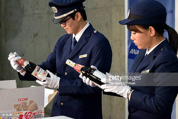 Custom officers examine bottles of Beaujolais nouveau arriving at the Kansai International Airport on October 29 2016 in Izumisano Osaka Japan The...