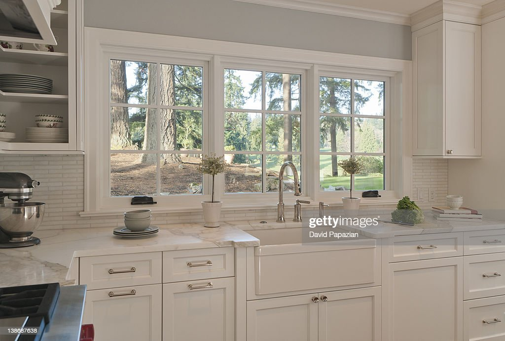 Custom white kitchen with view of park.