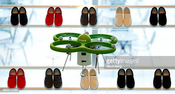 A custombuilt drone developed for Crocs Japan GK flies over shelves displaying pairs of Crocs Inc Norlin sneakers during a media preview at the...