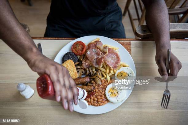 A customer adds tomato sauce to the 'Super' full English breakfast at the 'Enough to Feed an Elephant' cafe in this arranged photograph in London UK...