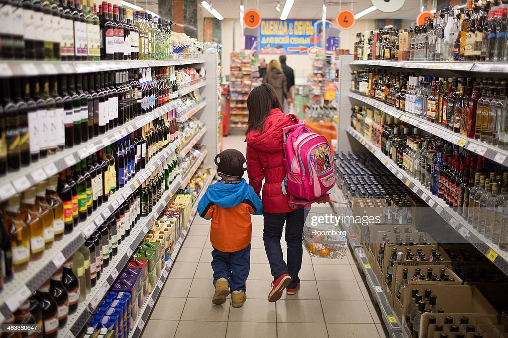 A customer and a child walk along the alcohol aisle inside a Dixy supermarket operated by OAO Dixy Group in Moscow, Russia, on Tuesday, April 8, 2014. Suppliers suffering from ruble depreciation this quarter are urging retailers to increase prices. Photographer: Andrey Rudakov/Bloomberg via Getty Images