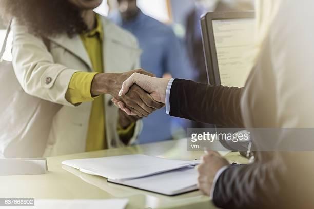 Customer and bank teller shaking hands