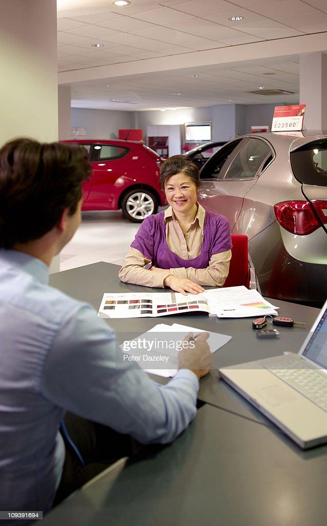 Customer and car salesman in car showroom : Stock Photo