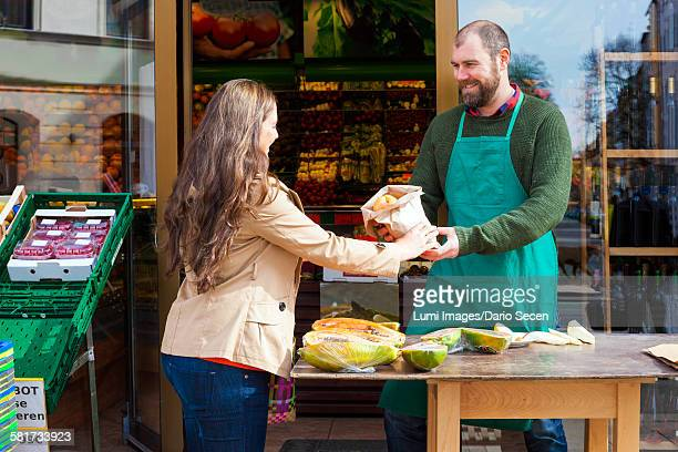 Customer and grocer in front of greengrocers shop