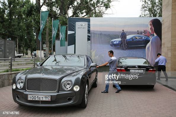 A customer approaches his Bentley automobile after inspecting new marques inside the Bentley Motors Ltd dealership in Almaty Kazakhstan on Thursday...