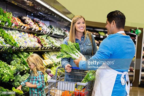 Customer asking produce manager for help in supermarket