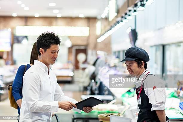 顧客からの質問のスタッフにデジタルタブレットのスーパーマーケット