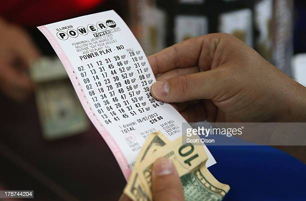 A customer at a 7Eleven store checks the numbers on his Powerball lottery ticket on August 7 2013 in Chicago Illinois The Powerball jackpot for...