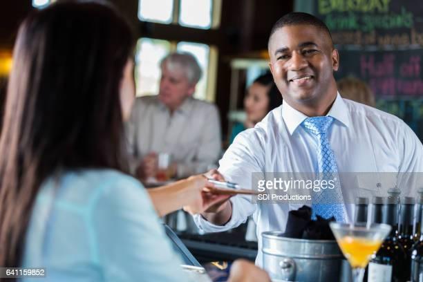 Customer at a bar hands bartender signed credit card receipt