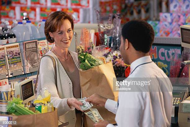 Customer at grocery checkout receiving change from clerk