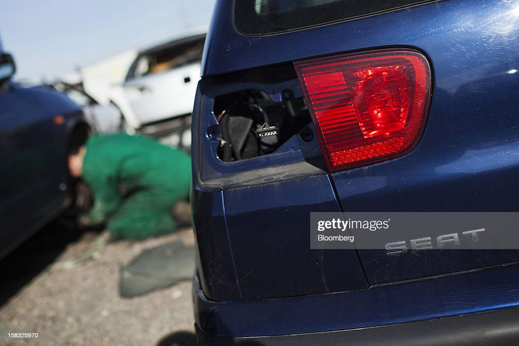 A customer attempts to remove a vehicle part near a scrapped Seat automobile in the yard of the Desguaces La Torre scrapyard in Madrid, Spain, on Thursday, Dec. 13, 2012. Spain has completed the debt sales it planned for this year and started raising funds for 2013, buying time for Prime Minister Mariano Rajoy as he decides whether to seek a European bailout. Photographer: Angel Navarrete/Bloomberg via Getty Images