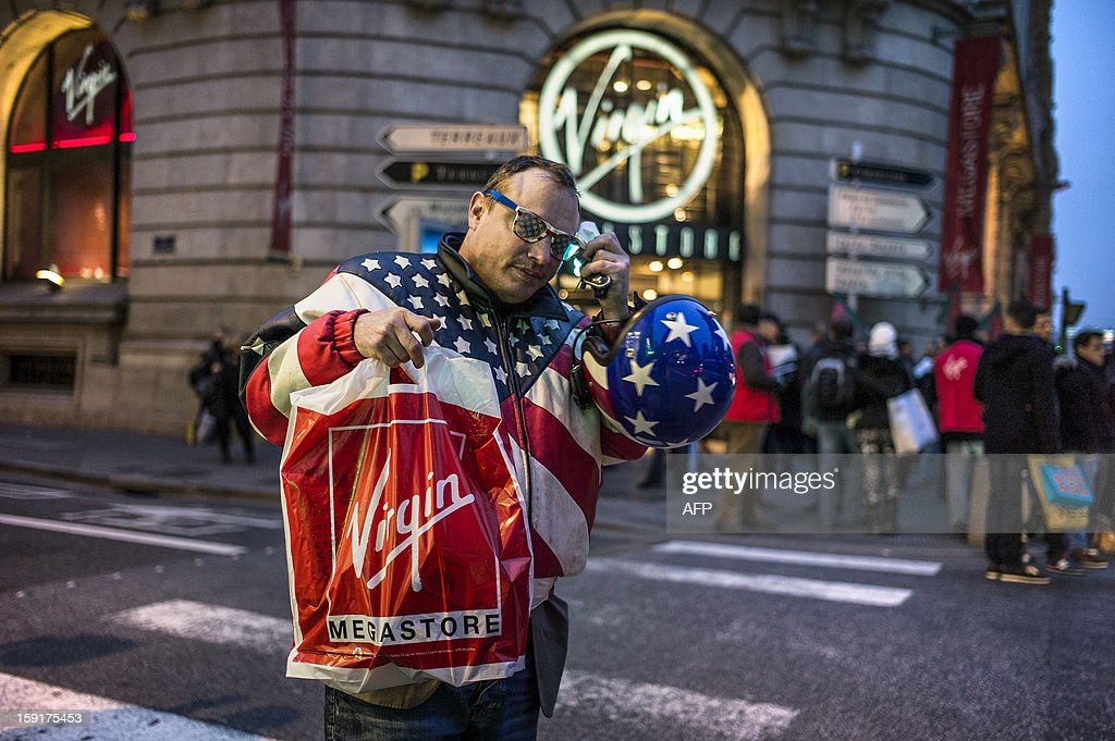 A customer bearing colors of the US flag stands in front of a Virgin Megastore during a demonstration against planned job cuts at the entrance of the store on January 9, 2013 in Lyon. Virgin's Megastore music and book unit, which is known in France as a 'culture' retailer, said it will file for insolvency on January 9, 2013. Originally started by Richard Branson, the British billionaire and chairman of the Virgin Group, the Virgin Megastores were bought by the French Lagardere group in 2001.