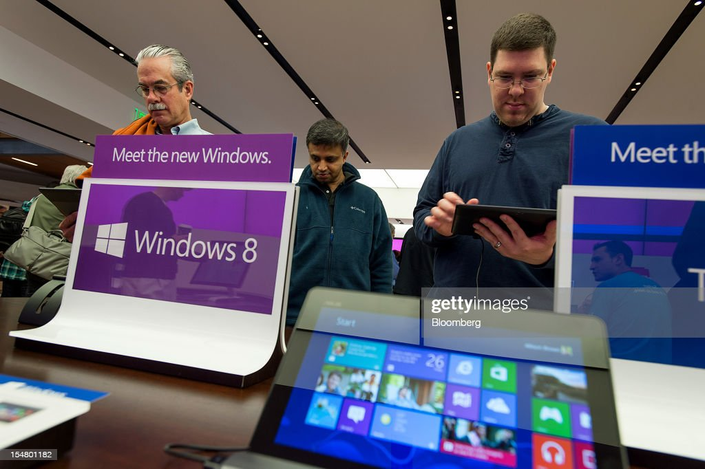Customer Ben Higginbotham, left, uses the Surface table computer at the opening of a Microsoft Corp. store in Bellevue, Washington, U.S., on Friday, Oct. 26, 2012. Microsoft Corp. introduced the biggest overhaul of its flagship Windows software in two decades, reflecting the rising stakes in its competition with Apple Inc. and Google Inc. for the loyalty of customers who are shunning personal computers and flocking to mobile devices. Photographer: Stuart Isett/Bloomberg via Getty Images