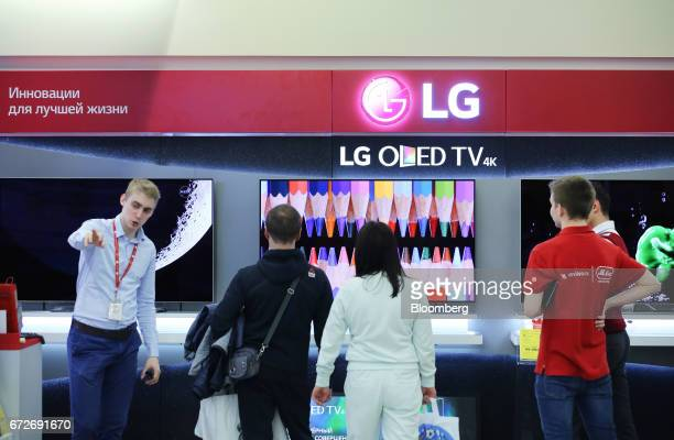 Customer browse a demonstration screen for the LG Electronics Inc 4K Oled television screens inside an MVideo PJSC electronics store inside the Mega...